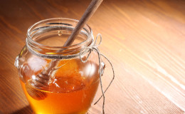 Pot of honey and wooden in it.  Object is on wooden table.